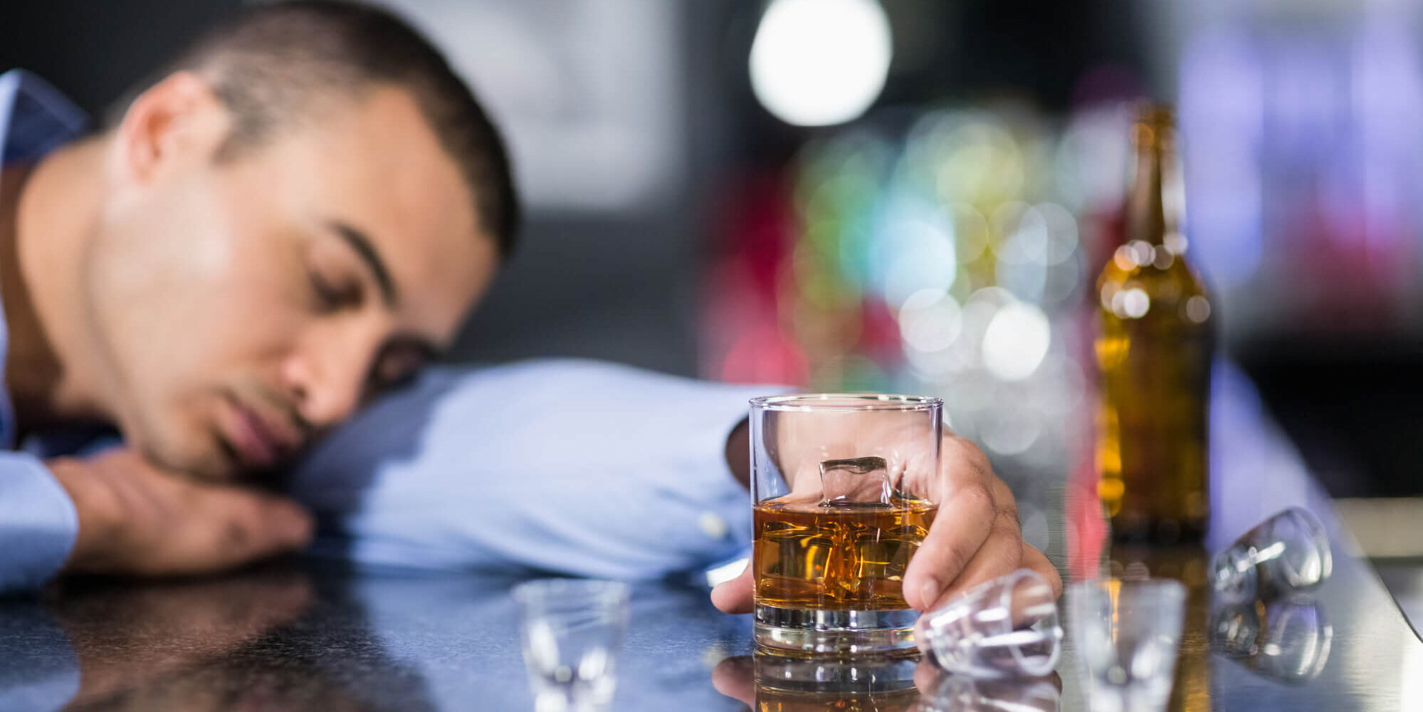 Man asleep at bar drinking whiskey to illustrate use of alcohol as a dysfunctional coping mode used to distract and numb feelings that people do not wish to deal with.