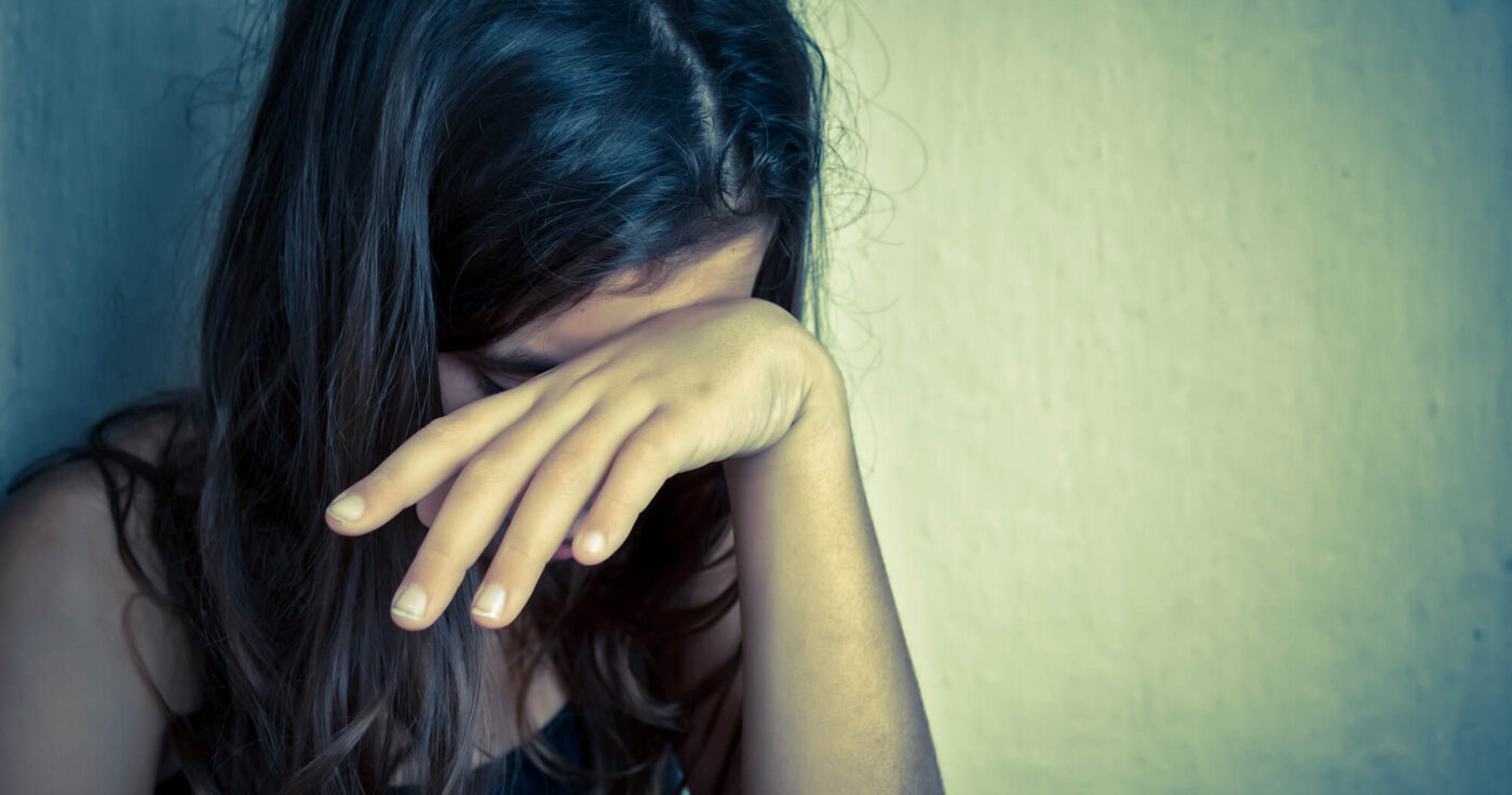 Image of a girl covering her face with hand representing a sad, lonely child with unmet emotional needs